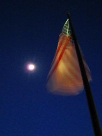 The moon illuminates the waving flag outside of the Parmenter building in downtown Muskegon.