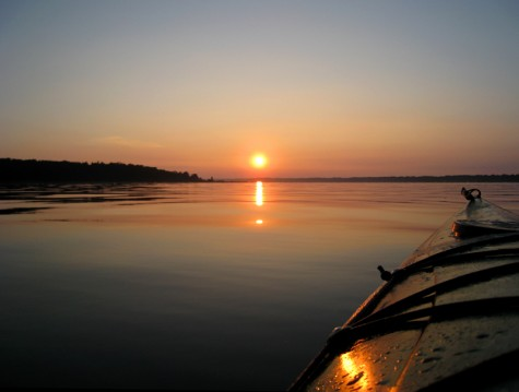 The sunrise is reflected off the hull of a kayak heading across Muskegon County's White Lake