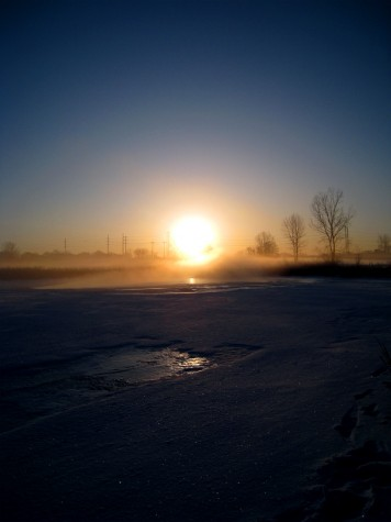 The sunrise through the morning fog across an icy Muskegon Lake on February 19, 2010